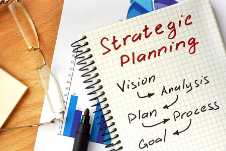 strategic: Notepad with Strategic planning concept on a wooden board.