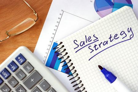 estrategia: Bloc de notas con la estrategia de ventas de conceptos sobre un tablero de madera.