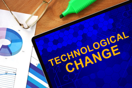 technological: Tablet with Technological Change and charts on a wooden board. Stock Photo