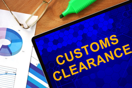 declaration: Tablet with Customs Clearance and charts on a wooden board. Stock Photo