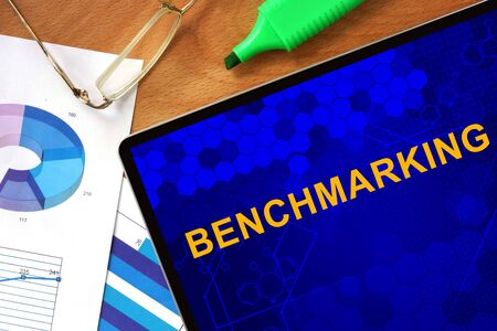 criterion: Tablet with Benchmarking and charts on a wooden board. Stock Photo