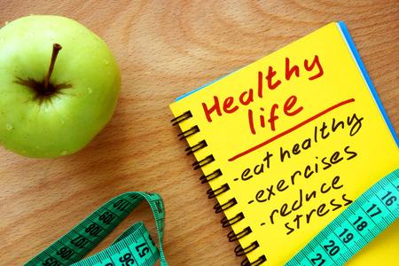 habitos saludables: Libreta con la manzana sana guía la vida y cinta métrica