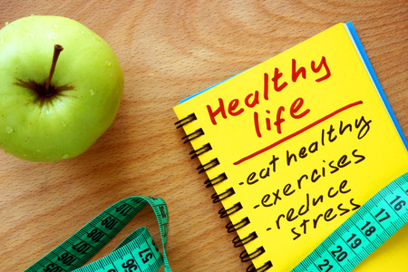 well: Notepad with healthy life guide apple and measure tape Stock Photo