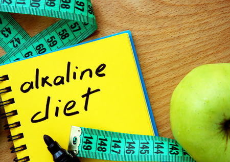 ph: Notepad with alkaline diet apple and measure tape