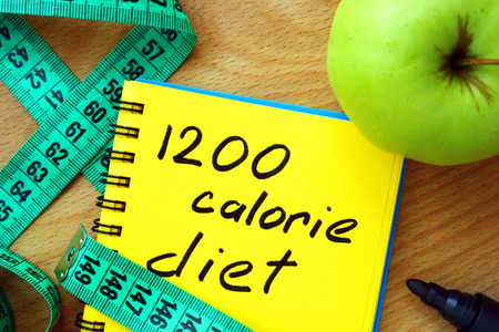 low: Notepad with 1200 calorie diet apple and measure tape Stock Photo