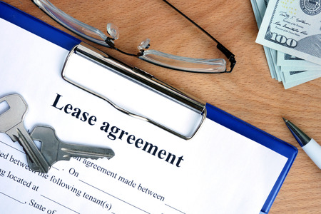 agreement: Lease agreement document with money on a wood background