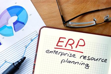 competitividad: Bloc de notas con el sistema de planificaci�n de recursos empresariales ERP en mesa de madera de la oficina. Foto de archivo