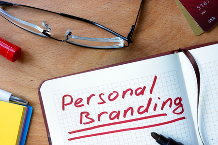 brand: Notepad with Personal Branding on office wooden table.