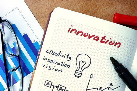 business innovation: Notepad with Innovation on office wooden table.