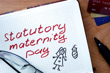 maternal: Notepad with statutory maternity pay on office wooden table.