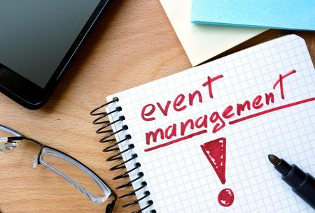 Notitieblok met event management op kantoor houten tafel. Stockfoto