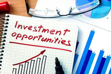 ingresos: Bloc de notas con las oportunidades de inversión en mesa de madera de la oficina.