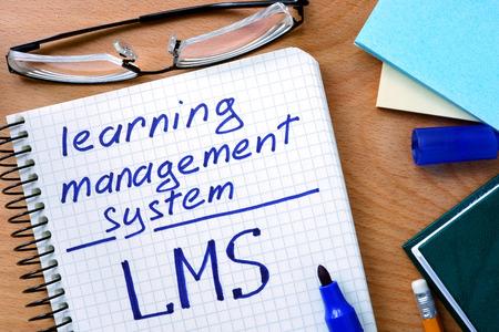 Bloc-notes avec LMS système de gestion de l'apprentissage sur le bureau table en bois.
