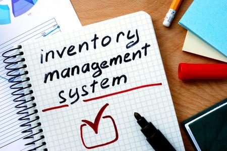inventario: Bloc de notas con el sistema de gestión de inventario en mesa de madera de la oficina.