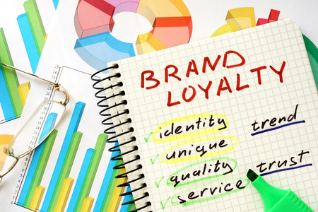 brands: Note with words brand loyalty on a wooden background. Stock Photo