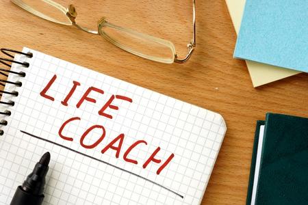 Opmerking met woorden life coach op een houten achtergrond.