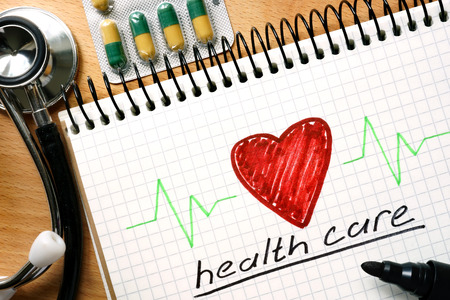 escalating: Note with words HEALTH CARE concept on a wooden background.