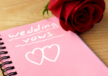 vows: Pink notepad with wedding vows and rose. Stock Photo