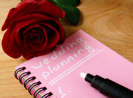 planning: Pink notepad with wedding planning and rose. Stock Photo