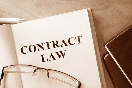 contracting: Book with words contract law and glasses.