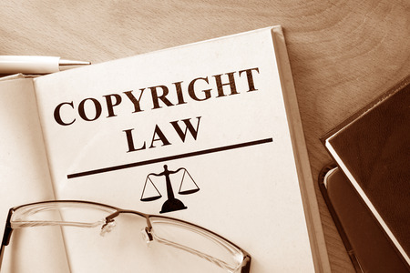 copyrighted: Book with words Copyright Law and glasses. Stock Photo