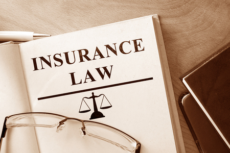 jurisdiction: Book with words Insurance Law and glasses. Stock Photo