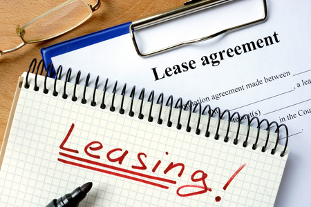 auto leasing: Notepad with leasing and lease agreement form.
