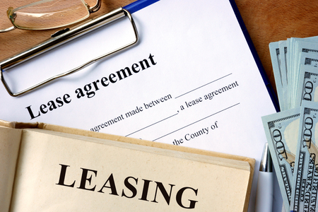 Book with word leasing, lease agreement form and money.