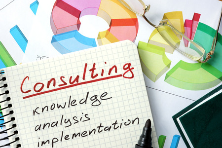 consultant: Consulting word written on the notepad and chart. Stock Photo