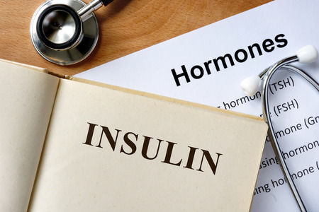 insulin: Insulin word written on the book and hormones list.