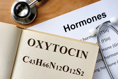 Oxytocin word written on the book and hormones list.