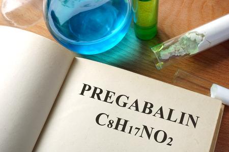 fibromyalgia: Book with Pregabalin and test tubes on a table.