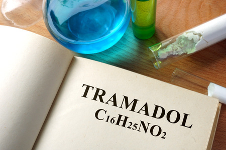 generic drugs: Book with tramadol and test tubes on a table. Stock Photo