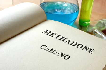 opiate: Book with methadone and test tubes on a table.