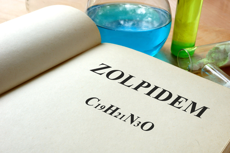 anticonvulsant: Book with Zolpidem and test tubes on a table.