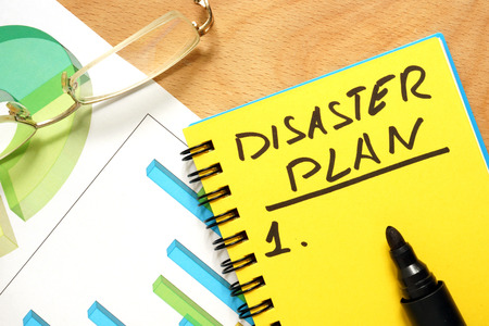 disaster recovery: Notepad with disaster plan on a wooden table. Stock Photo
