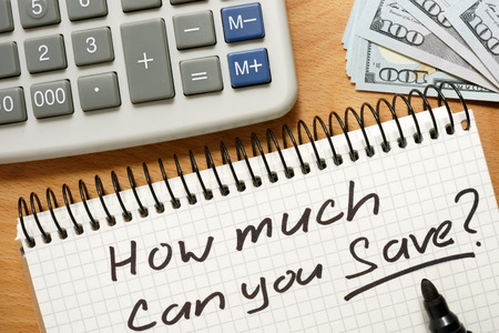 Notepad with how much can you save on a wooden table. Home budget concept. Stockfoto