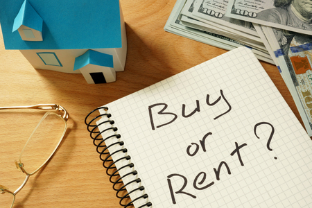 buying questions: Notepad with buy or rent, home model and dollars. Real estate concept.