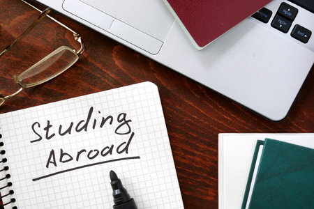 Studying Abroad concept on a paper with notebook. Stock Photo