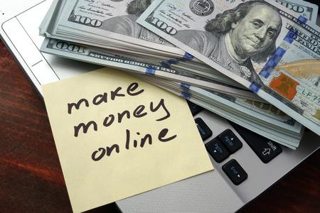 돈을 벌 노트북을 사용 하여 종이에 온라인 개념.