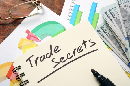 trade secret: Trade Secrets written on notebook with charts.