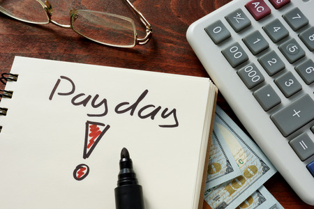 payday: Payday written on notebook with dollars.