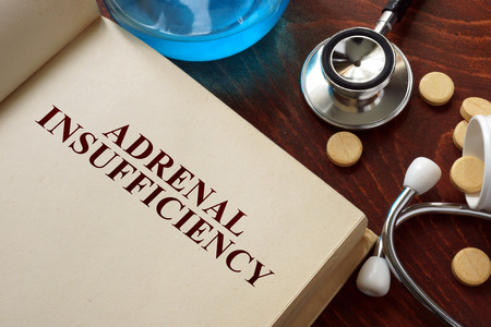 congenital: Adrenal insufficiency written on book with tablets.