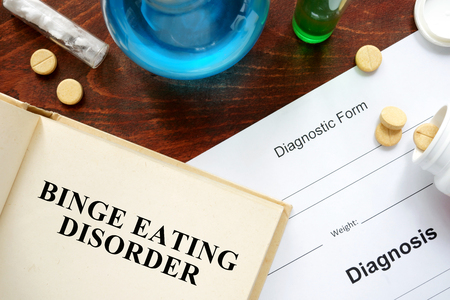 binge: binge eating disorder written on book with tablets. Stock Photo