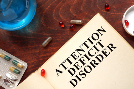 inhibitory: attention deficit disorder written on book with tablets.