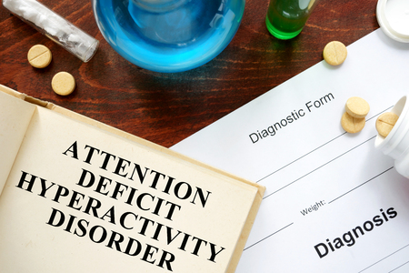 deficit: attention deficit hyperactivity disorder written on book with tablets.