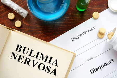 bulimia: bulimia nervosa written on book with tablets.
