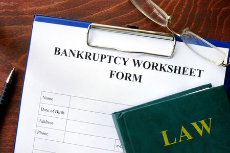 banking problems: Bankruptcy worksheet form on a wooden table.
