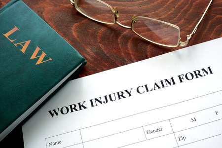 Work injury claim form on a wooden table. Banco de Imagens