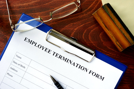 unfair: Employee termination form on a wooden table.